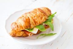 与火腿咸味干乳酪芝麻菜的三明治新月形面包 免版税库存照片