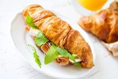 与火腿咸味干乳酪芝麻菜的三明治新月形面包 免版税图库摄影