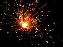 与火花的闪烁发光物在黑背景 免版税图库摄影