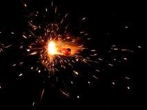 与火花的闪烁发光物在黑背景 免版税库存照片