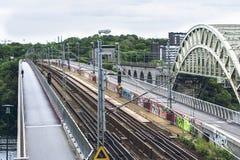 与火车和步行桥的城市风景 免版税库存照片