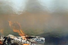 与火闷燃的被烧焦的木和红色火焰的背景  库存照片