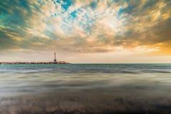 与灯塔和剧烈的天空的最小的海场面 库存图片
