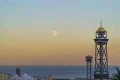 与灯塔和月亮的日落视图 库存图片