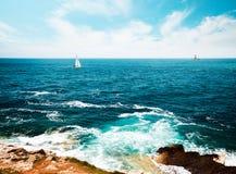 与灯塔和航行游艇的被定调子的海景 免版税库存照片
