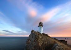 与灯塔的晚上风景。 库存照片
