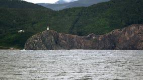 与灯塔的礁石 图库摄影