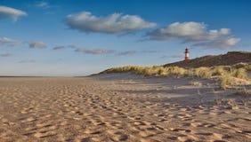 与灯塔的离开的海滩在沙丘后 免版税库存照片