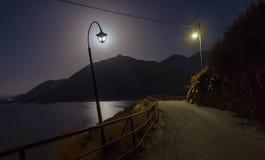 与灯的夜风景在路、山、海和月亮附近 免版税库存图片