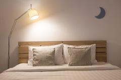与灯的白色逗人喜爱的卧室内部 库存图片