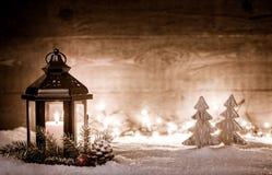 与灯笼、树、冷杉分支、雪剥落和被弄脏的光的圣诞节场面在一个被阐明的黑暗的木板前面  库存照片