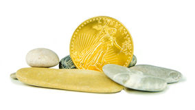 与灰色小卵石石头的金黄美国老鹰硬币 免版税库存图片