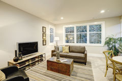 与灰色沙发和树干咖啡桌的家庭娱乐室内部 免版税库存照片