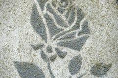 与灰色玫瑰的图象的装饰膏药在房子墙壁上的  背景或纹理 特写镜头,软的焦点 图库摄影