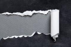 与灰色空间的被撕毁的黑色纸张消息的 免版税库存图片