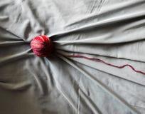 与灰色织品的红色羊毛球 库存照片