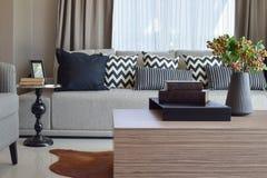 与灰色镶边枕头的时髦的客厅设计在沙发 免版税库存图片