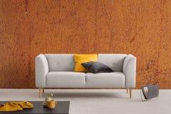 与灰色长沙发的被烧的橙色wabi sabi客厅内部有黄色和黑枕头和报架的 库存图片