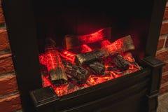 与灼烧的木柴的真正的壁炉 库存照片