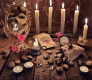 与灼烧的蜡烛、不可思议的镜子、花和占卜用的纸牌的神秘的仪式 免版税库存图片