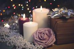 与灼烧的蜡烛、圣诞节装饰和礼物盒的静物画 免版税库存图片