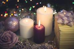 与灼烧的蜡烛、圣诞节装饰和礼物盒的静物画 免版税库存照片