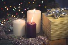 与灼烧的蜡烛、圣诞节装饰和礼物盒的静物画 免版税图库摄影