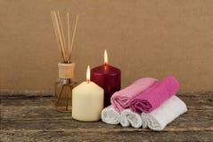 与灼烧的蜡烛和温泉毛巾的美好的构成在木背景 库存照片