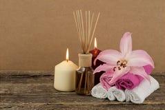 与灼烧的蜡烛和芳香油的美好的构成在木背景 免版税库存照片