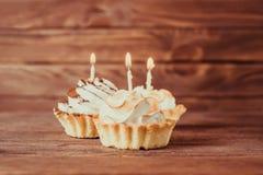 与灼烧的蜡烛的三块假日杯形蛋糕 库存图片