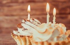 与灼烧的蜡烛的甜杯形蛋糕 库存图片