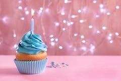 与灼烧的蜡烛的生日杯形蛋糕在桌上 免版税库存照片