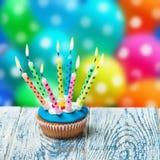与灼烧的蜡烛的生日杯形蛋糕 库存图片