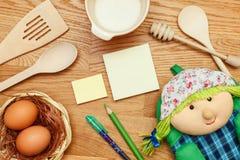 与炊事用具的笔记薄在木桌上 顶视图 免版税库存图片