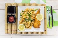 与炒米的油煎的鳕鱼在一竹placemat 库存照片
