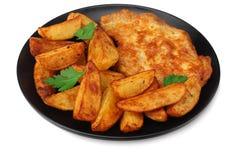 与炸肉排的油煎的土豆楔子在白色背景隔绝的黑色的盘子 库存照片