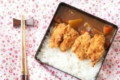 与炸鸡和菜的顶视图日本咖喱饭顶部在有筷子的黑色的盘子 免版税库存图片