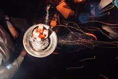 与炽热煤炭的Shisha水烟筒 火花从呼吸 与椰子木炭为放松和shisha烟的现代水烟筒 库存图片