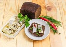 与烂醉如泥的大西洋鲱鱼切片的单片三明治在棕色brea 免版税库存图片