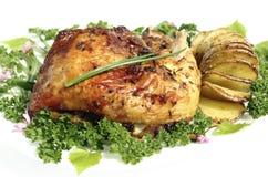 与烘烤土豆hasselback的炸鸡大腿 库存图片