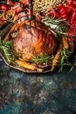 与烘烤菜的传统烤圣诞节火腿在有欢乐假日装饰的葡萄酒板材在黑暗的土气背景 免版税库存照片