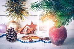 与烛光、冷冻苹果和冷杉分支的圣诞卡片在木背景 图库摄影