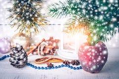 与烛光、冷冻苹果和冷杉分支的圣诞卡片在木背景 库存照片