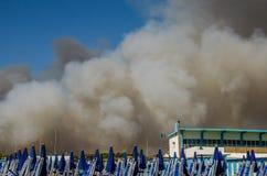 与烟云的火在与蓝色伞和太阳懒人的海滩在Ostia,意大利 免版税图库摄影
