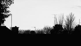与烟囱和天线的剪影都市地平线 免版税图库摄影