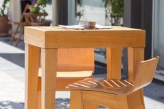 与烟灰缸的木在大阳台的咖啡桌和凳子 免版税图库摄影