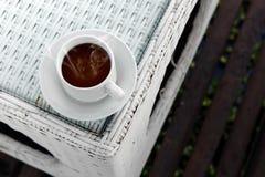 与烟的热的咖啡在白色玻璃桌上 库存图片