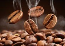 与烟的特写镜头落的咖啡豆在棕色背景 免版税库存照片