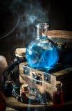 与烟的蓝色魔药在木箱 黑暗的不可思议的概念 库存图片