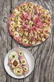 与烟肉乳酪在老木野餐桌上和蕃茄三明治的开胃菜美味盘设置的蛋腌火腿 免版税库存图片